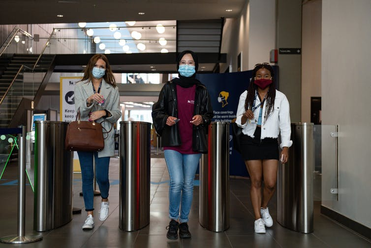 Three university students walk through an electronic barrier.
