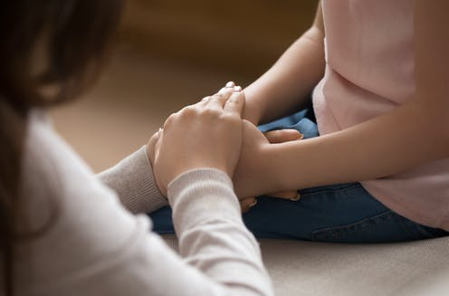 An adult clasps a child's hand in hers