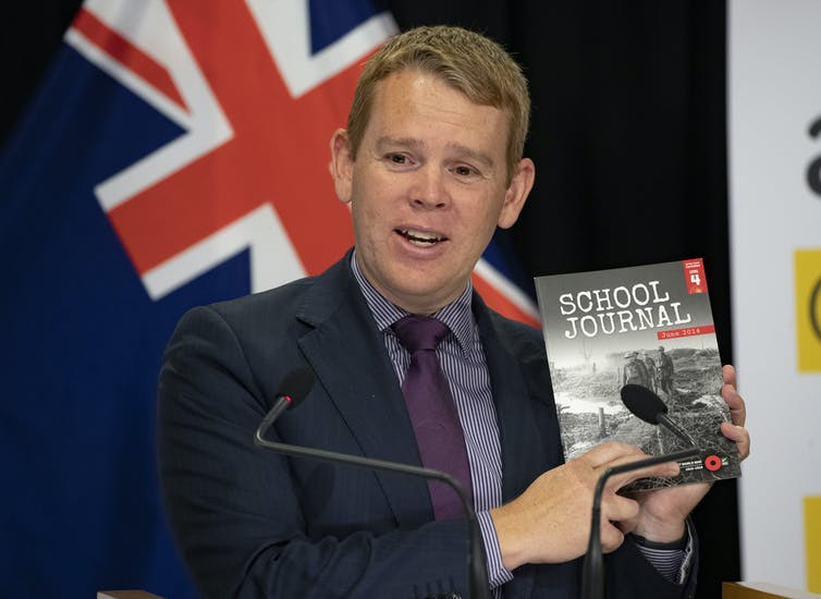 Chris Hipkins holding a school journal