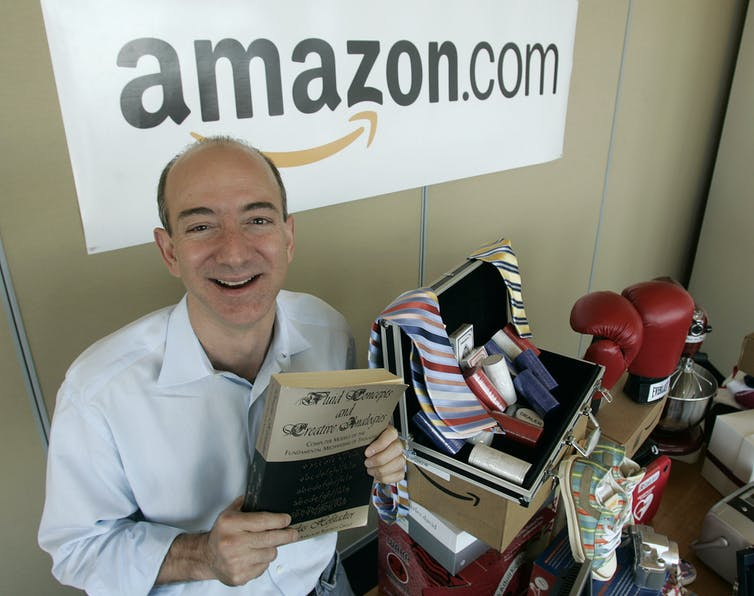 Jeff Bezos holding the first book he ever sold.