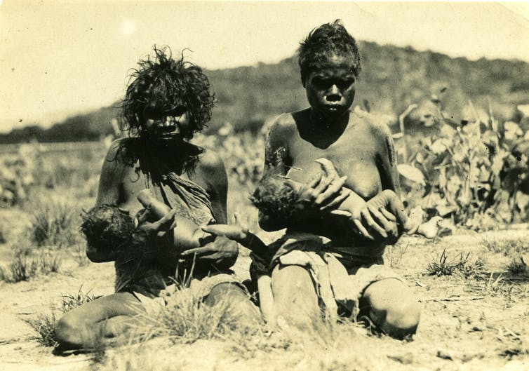 Gurrhwek Mangiru (left) with baby Gurrhwek Mangiru (left) Albert Balmana, and unidentified woman and baby (right), Oenpelli, Northern Territory Archives Service.