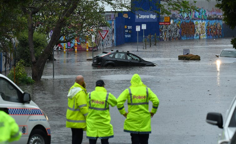 Emergency staff look on as cars and houses are flooded.