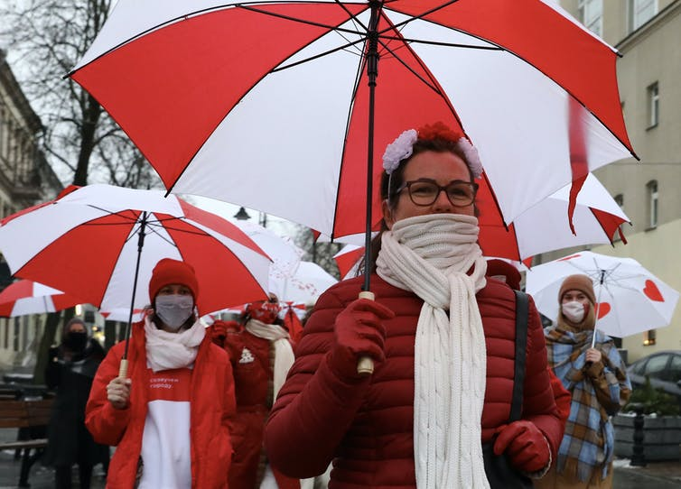 Protesters march in the Belarus capital Minsk carrying umbrellas and wearing the red and white colours of the protest movement.