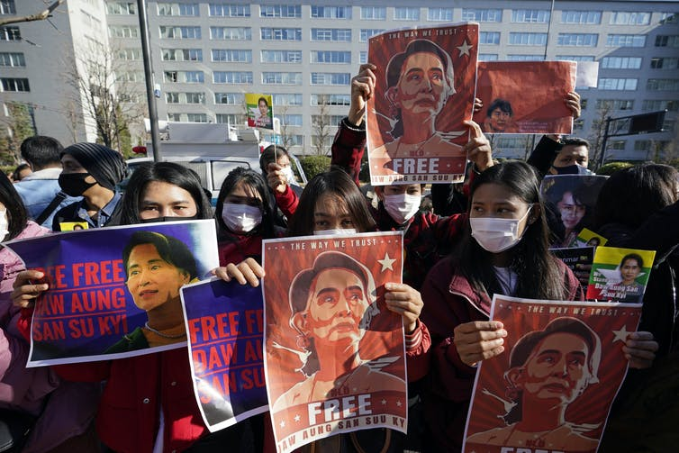 Masked Burmese protesters carrying pictures of Aung San Suu Kyi.