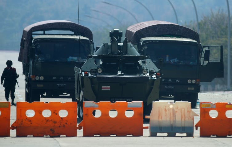 An army tank and personnel carriers behind a road block.