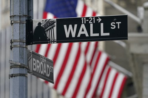 A Wall Street street sign with the American flag in the background.