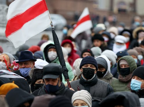 Crowded street full of protesters wearing masks and carrying flags of the Belarus protest movement.