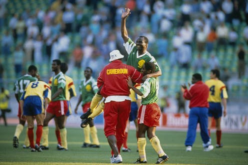 A smiling man in football gear raises a hand in the air as he is held aloft by two other players, one in a red tracksuit with the word Cameroun in yellow, other players and arrows of spectators in the background.