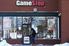 A customer checks on his cellphone as he walks to a GameStop store.
