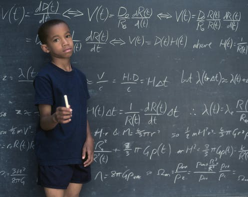 A Black boy holds a piece of chalk while standing by a chalk board filled with math equations.