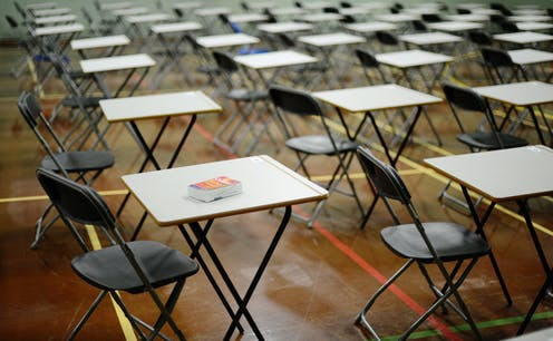 Empty chairs and desks in an exam hall.