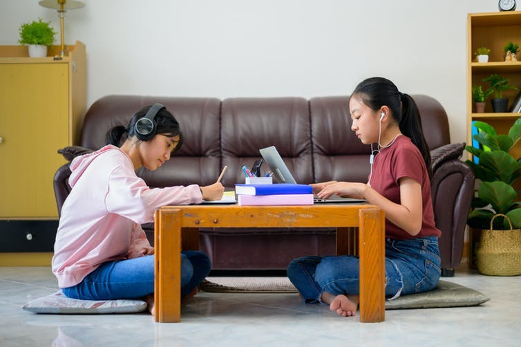 Two girls study at a coffee table.