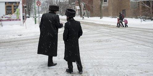 Two Hasidic men converse on a street.