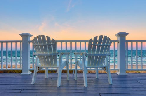 Two empty white adirondack chairs facing the ocean