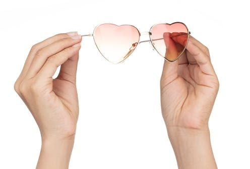 Hands holding a pair of pink-tinted heart-shaped glasses