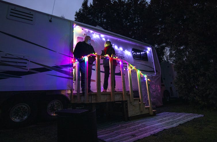 A couple standing on the steps of their trailer at dusk, with decorative lights.