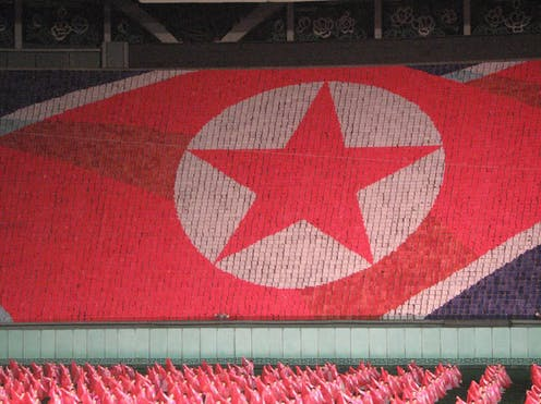 the North Korean flag formed by people in a stadium holding colored cards