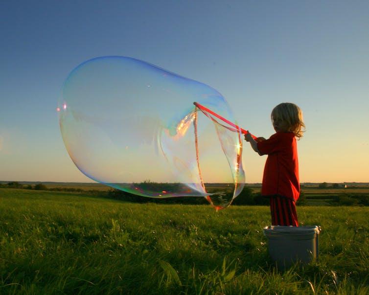 A boys makes a large soap bubble.