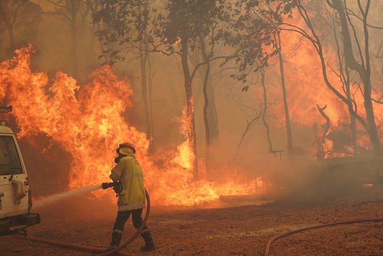 A firefighter battles a blaze with a hose
