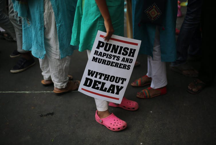 A woman carries a placard which reads: punish rapists and murderers without delay.