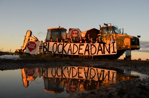 A protest group holds a sign 'Blockade Adani'
