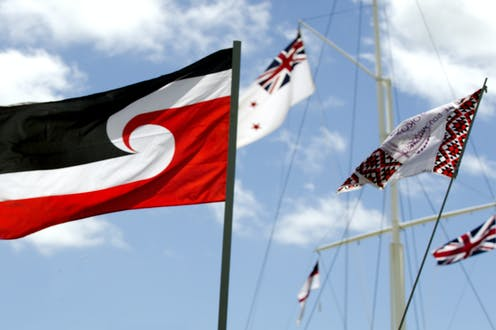 Tino Rangatiratanga flag with other flags against blue sky