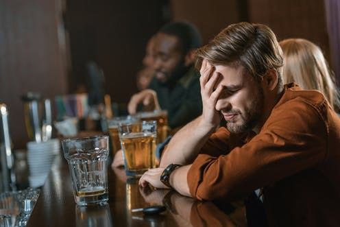 Person drinking at bar with head in hands looking confused
