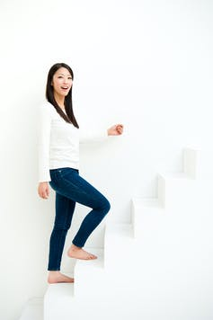 A woman climbing a white staircase