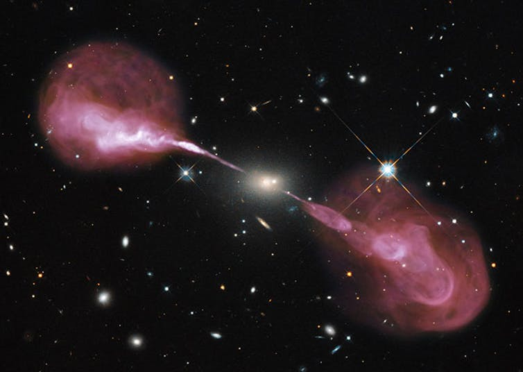 Radio galaxy with bright yellow core, long thin jets extending in opposite directions and large red lobes