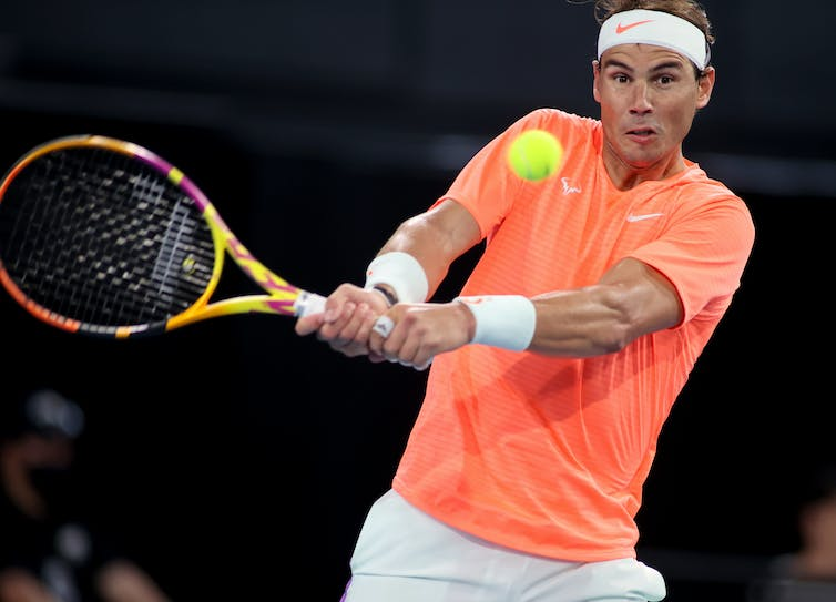 Rafael Nadal holding a tennis racket and about to hit a ball.