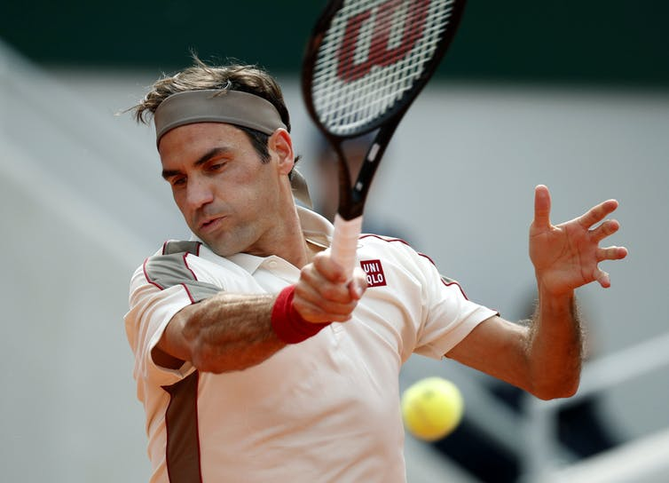 Roger Federer swinging the racket and about to hit a tennis ball.