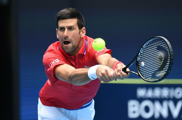 Novak Djokovic stretching with both hands on the racket about to hit the tennis ball.