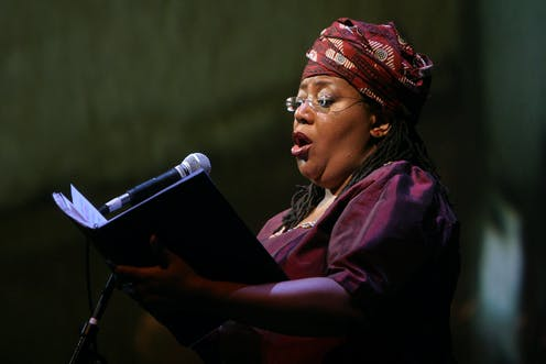 A woman dressed in purple, her hair covered by a traditional cloth and wearing glasses, sings into a mic as she reads music that she holds.