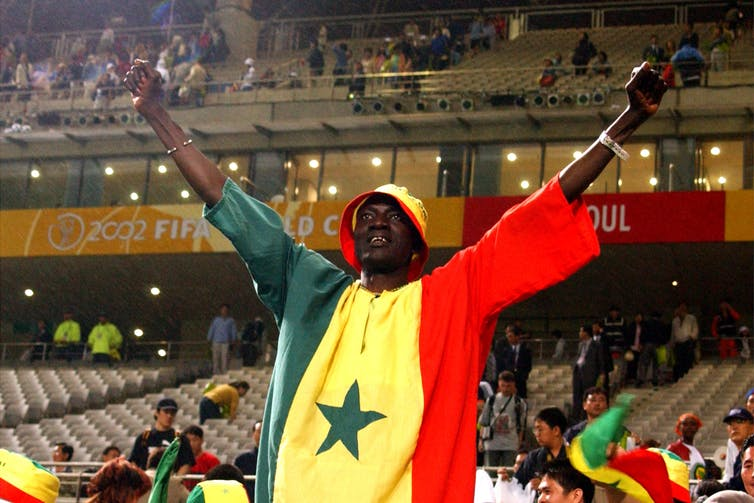 A man stands with two fists in the air, wearing a shirt comprised of the colours of the flag of Senegal - green, yellow and red, behind him a sports stadium.