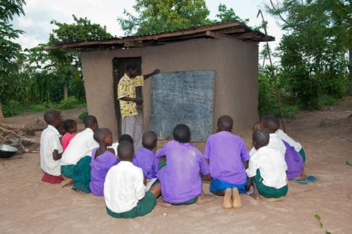 Children sit on the ground outside a small building while a man points to a blackboard on the exterior wall of the building
