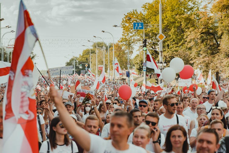 People protesting in streets in Belarus holding red and white flags.