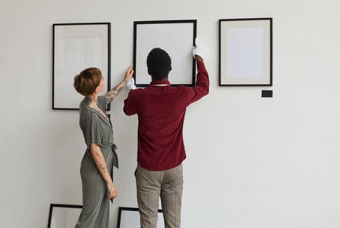 Woman touches frame while man holds it in place against gallery wall