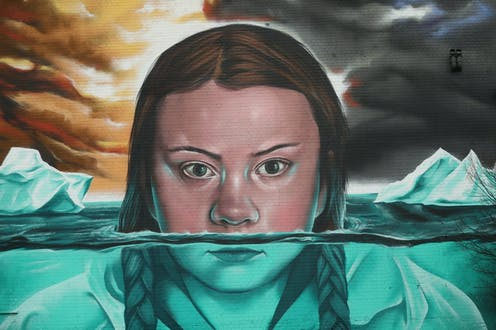 A mural depicts Greta Thunberg submerged amid ice floes.