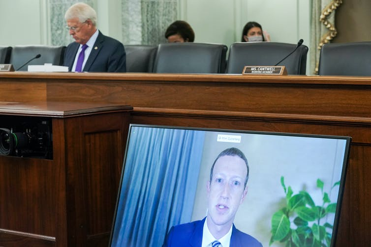 A screen showing Mark Zuckerberg lies against a desk in the US senate for a hearing