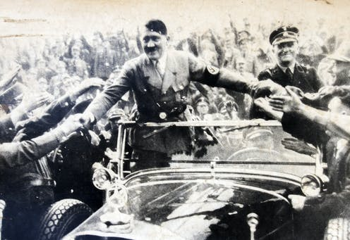 Adolf Hitler riding in an open car greeting supporters.