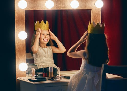 A young girl places a crown on her head while looking in the mirror.