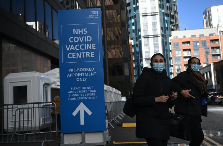 Two people leaving a UK COVID vaccination centre