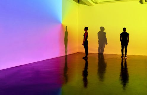 people standing in front of color projections on wall