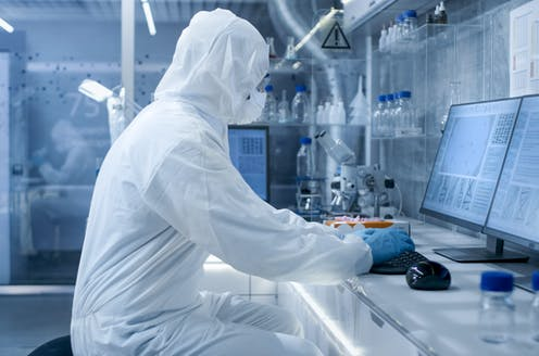 A scientists in PPE working in a lab