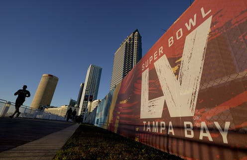 A man running past signage for the 55th Super Bowl.