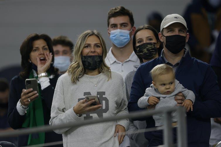 افرادی که نزدیک به هم ایستاده اند و بیشتر آنها ماسک دارند.