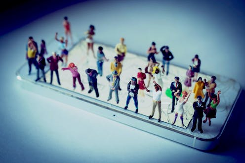 Miniature people standing on a smartphone