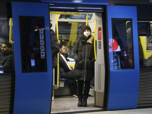 A woman wears a mask on a stockholm train.