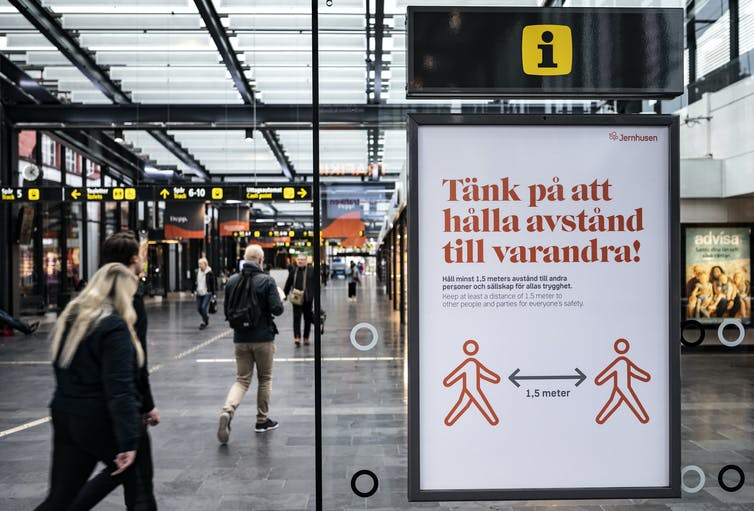 A sign at a train station encourages people to keep their distance from one another in Swedish.