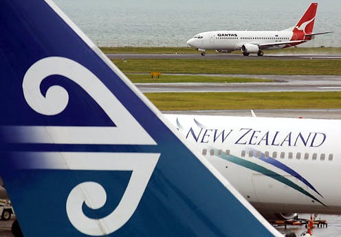An Air New Zealand passenger plane at Auckland Airport with a Qanta plane in the background